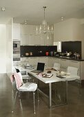 Crystal chandelier above modern dining set in black and white fitted kitchen