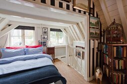 Double bed next to head of staircase in white, wood-clad attic room; wallpaper with wide stripes, ornamental bird cage and bookcase in foreground