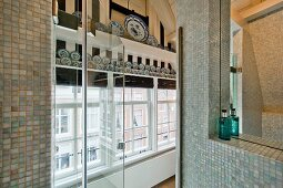 Shower cabinet with glass door and mosaic tiles; view of gable-end windows and blue and white decorative plates
