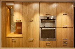 Kitchen cupboards with wooden fronts and stainless steel handles, fitted appliances and integrated aperture with view of staircase