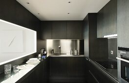 Dark designer kitchen with stainless steel splashback and hatch above narrow counter