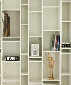 Books, jointed doll and small hifi on white fitted shelving with compartments of different sizes