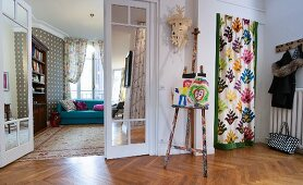 Colourful curtain screening niche in foyer, easel, double doors and view into living room