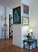 Framed pictures on hallway wall in period apartment with herringbone parquet floor