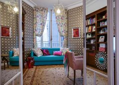 Light blue couch in front of window with draped curtains and patterned wallpaper in eclectic interior seen through open double doors