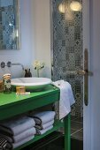 Green-painted washstand with countertop sink next to shower area with black and white patterned wall tiles