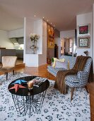 Delicate coffee table and black and white, fifties-style couch in open-plan interior