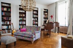 Sofa with colourful patterned cover in front of bookcases and antique piano