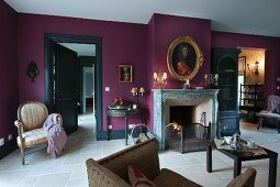 Gilt-framed portrait on purple-painted wall above fireplace