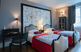 Twin beds with red covers against large framed panel of toile de jouy next to writing desk