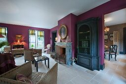 Fireplace next to black display cabinet in lounge with purple-painted wall and pale tiled floor