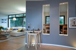 Curved wall with two interior windows in front of sofa combination and dining room