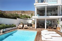 Sunny pool and wooden deck with pale futon loungers outside contemporary house in Mediterranean landscape