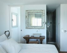 View across bed to rustic washstand below framed vintage mirror and Tolomeo standard lamp in bedroom