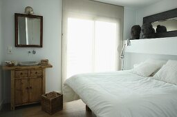 Double bed with white bed linen next to window and rustic chest of drawers with integrated sink