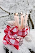 Lit candles in old glass scoop decorated with red ribbon and white Christmas baubles surrounded by snow