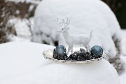 White stag ornament, metal fir cones and Christmas tree baubles on plate surrounded by snow