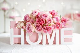 Pink roses in painted fruit crate and ornamental letters spelling 'HOME'