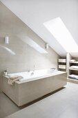 Bathtub in modern attic bathroom with sand-coloured tiles