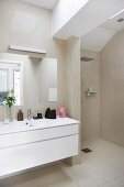Modern washstand with white base unit against beige-tiled wall next to floor-level shower