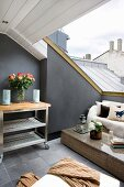 Wicker furniture and serving trolley in lounge area on roof terrace