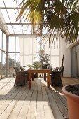Essbereich im Glashaus mit rustikalem Dielenboden, im Hintergrund bodenlange Vorhänge vor Glasfassade als Sonnenschutz