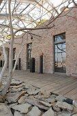 Altes Gewächshaus mit freigelegter Ziegelwand und Fenstern, davor Stelen mit Kunstobjekten auf Holzboden, im Vordergrund Naturstein Bruchstücke