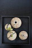 Verschiedene Gefässe teilweise mit Blumenzweig auf schwarzem Tablett