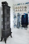 Antique, artistic stove and vintage-style shelves with coat hooks below on blue floral wallpaper