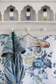 Shelves with perfume bottles in niches mounted on wall with blue floral wallpaper