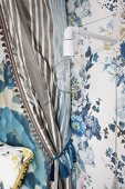 Minimalist sconce lamp on blue floral wallpaper next to draped canopy curtain