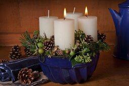 Rustikaler Adventskranz mit zwei brennenden Kerzen in einer blauen Gugelhupfform