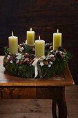 Rustikaler Adventskranz mit vier brennenden grünen Kerzen, Walnüssen, Moos und Zapfen als Deko