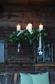 Rustikaler Adventskranz mit Tannengrün hängt an einer verwitterten Holzfassade