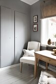Kitchen table and upholstered chair below window next to grey-painted cupboard door