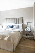Box-spring bed with pale valance and bedspread and upholstered headboard hung on wall painted pale grey in elegant bedroom