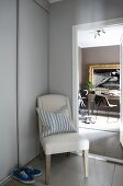 Chair with pale upholstery between open interior door and fitted cupboard
