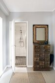 Vintage apothecary cabinet and mirror against pale grey wall next to open bathroom door