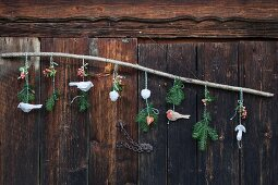 Branch festively decorated with hand-crafted felt bird pendants and sprigs of fir