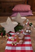 Hand-crafted felt glass sleeve next to wooden stars on festively decorated wooden table
