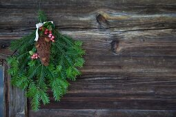 Green fir branches and hand-crafted felt fir cone hanging on rustic wooden wall
