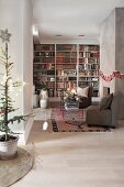 Elongated, festively decorated living room with bookcase and seating area in front of fireplace