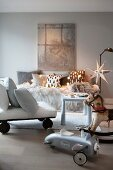 Festively decorated interior with sofa, chaise on large castors, rocking horse and ride-on toy car