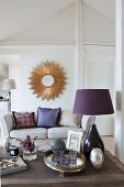 Purple table lamp on coffee table, sofa and sunburst mirror on wall