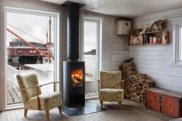 Fifties armchair next to fire in black, cast iron wood-burning stove in front of French windows with view of jetty