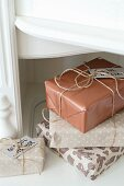 Stacked Christmas presents wrapped in gift paper in natural shades and tied with parcel string
