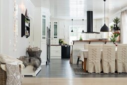 Loose-covered chairs with lacing in dining area of open-plan kitchen with black extractor hood above counter