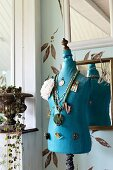 Blue tailors' dummy decorated with necklaces and brooches