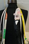 Tape measures and doll hanging on black tailors' dummy