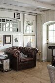 Brown leather armchair below collection of artworks on wall in rustic interior